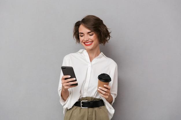 持ち帰り用のコーヒーを持ち、携帯電話を使用して、灰色の壁に隔離されたヨーロッパの女性