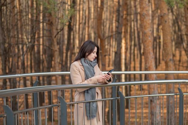 電話で探しているコートのヨーロッパの女性。秋市にて。高品質の写真