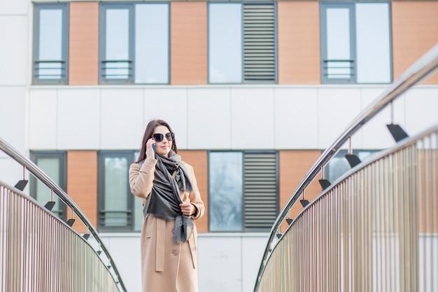 電話で話しているコートを着たヨーロッパの女性。秋市にて。
