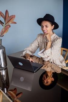 ドレスと古典的な帽子のヨーロッパの女性は、キッチンで自宅で働いています