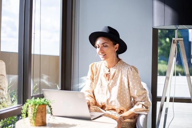 Европейская женщина в платье и классической шляпе работает дома на кухне