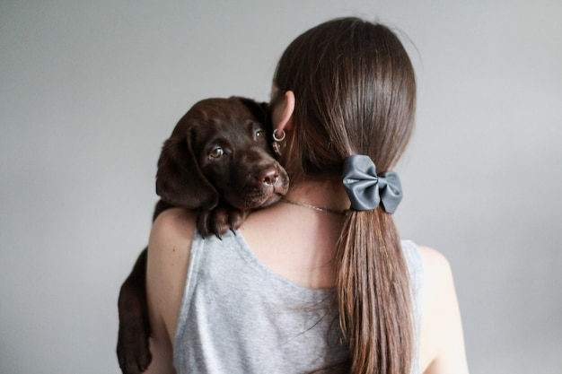 灰色の服を着たヨーロッパの女性は、チョコレート色のラブラドールレトリバーの子犬を保持します