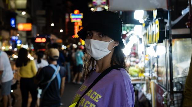 Donna europea in maschera facciale bianca medica nell'affollata città cinese di bangkok