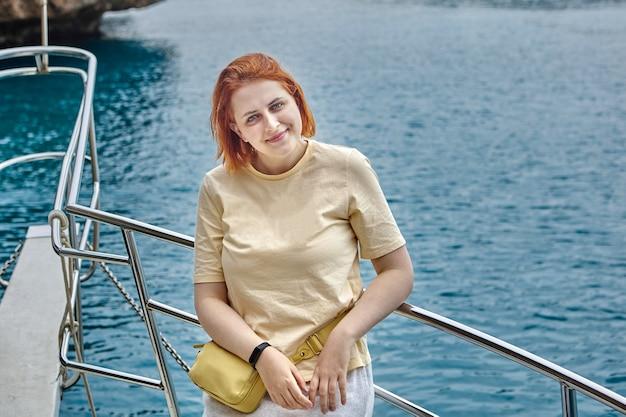 観光ヨットに乗って写真家をポーズするヨーロッパの女性。