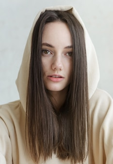 European woman's face brunette with long hair hooded close up, russian girl
