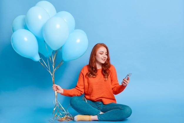 유럽 여자는 바닥에 앉아 헬륨 풍선의 무리를 들고, 장치의 디스플레이를보고 전화로 여성, 누군가를 그녀의 파티에 초대하도록 호출합니다.
