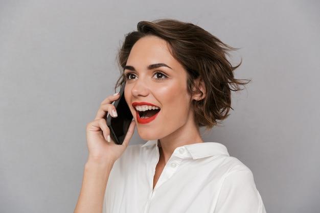 灰色の壁に隔離され、携帯電話で笑顔で話すヨーロッパの女性