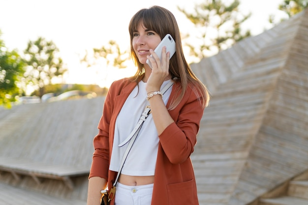 大学のキャンパスや近代的な公園を歩きながらモビル電話で話しているヨーロッパの女性。