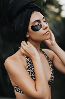 European woman in turban posing with closed eyes on nature background. outdoor shot of relaxed lady in swimsuit.
