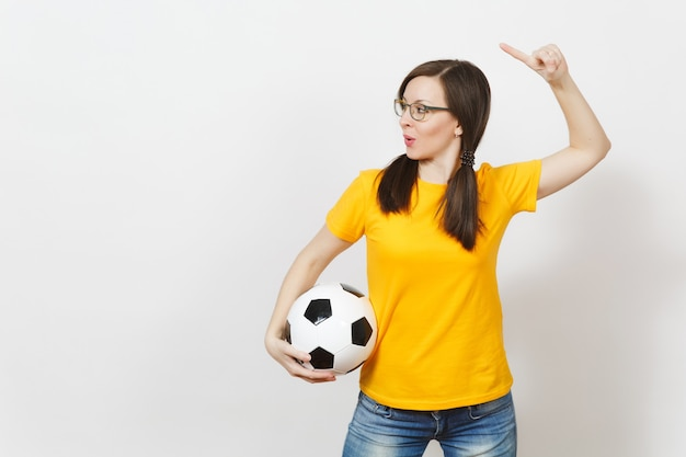 European woman, two fun pony tails, football fan or player in glasses, yellow uniform point finger aside, hold soccer ball isolated on white background. sport, healthy lifestyle concept. copy space.