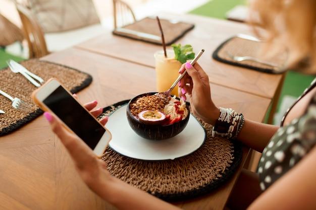 Donna europea che utilizza telefono cellulare nel caffè.