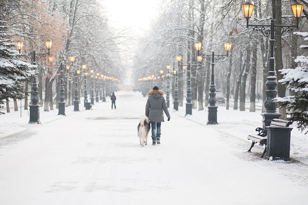 夕方の冬の街でアラスカンマラミュート犬と一緒に歩くヨーロッパの女性
