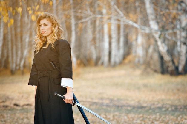 Европейская женщина с катаной в кимоно. девушка занимается боевыми искусствами. женщина в осеннем лесу. воин с холодным оружием в руках