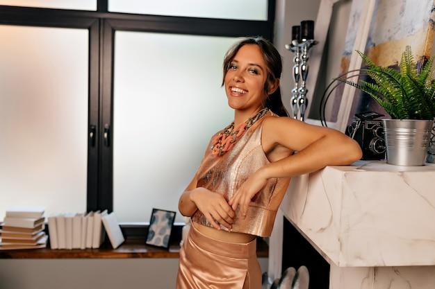 Donna europea con trucco luminoso in vestito elegante che prepara per la festa di compleanno