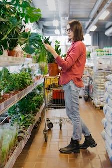 Европейская женщина с темными волосами в красной рубашке выбирает растения в саду гипермаркета женщина ландшафтный дизайнер