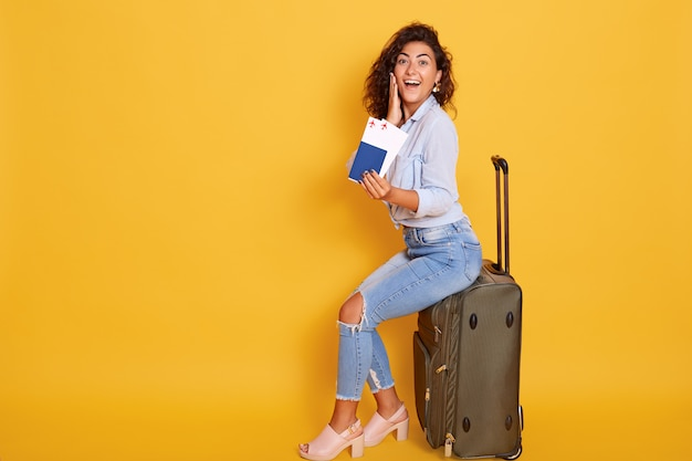 European woman with passport and ticket sitting on suitcase and looking happy and excited