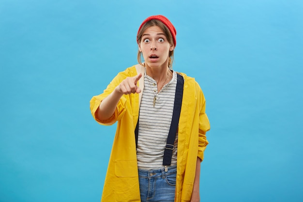 European woman with surprised expression dressed in yellow casual loose jacket pointing with index finger keeping her mouth wide open being shocked with what she sees. facial expressions