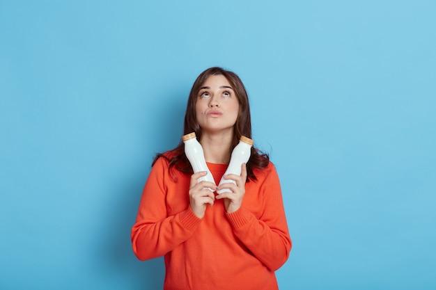 物思いにふける表情で見上げる、2本の新鮮なミルクを保持しているヨーロッパの若くて健康な白人女性、青い壁に隔離されたカジュアルなオレンジ色のセーターを着ているヨーグルトの女性。