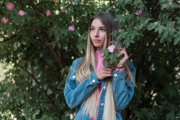 파란색 유행 데님 재킷에 유럽 젊은 매력적인 여자는 여름 날에 공원에서 녹색 꽃 덤불 옆에 서있다. 아름다운 매력적인 현대 여자 모델은 정원에서 휴식을 좋아합니다