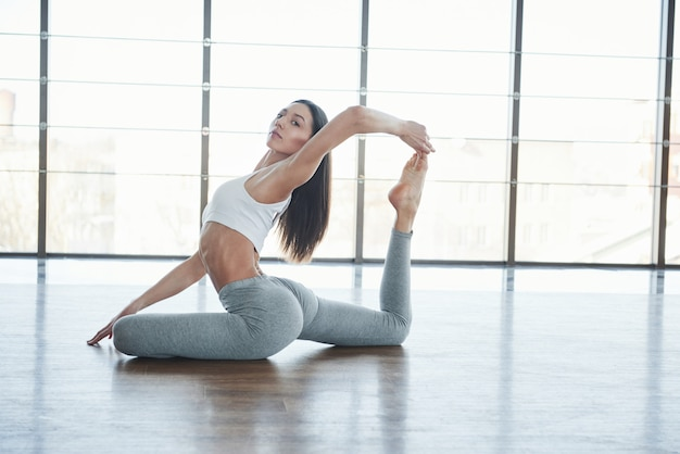 European young brunette doing yoga in the room with big windows