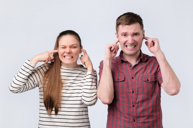 European young family couple woman and man closing ears because of unpleasant loud noise.