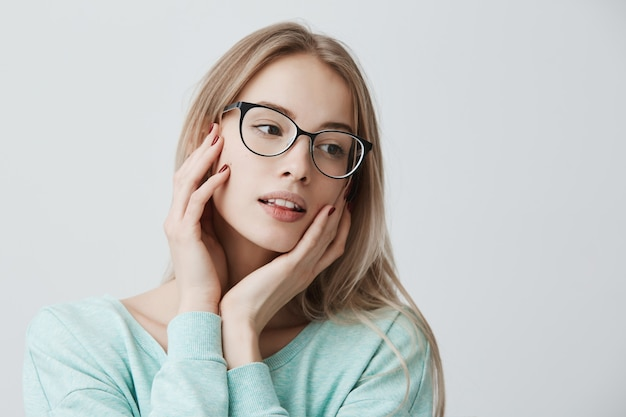 European young female with long blonde hair, wears spectacles and casual loose blue sweater, looks confidently and calmly, spends weekends alone, relaxes indoors, touches cheeks tenderly with hands.