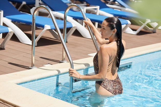 European young lady climbing out of swimming pool