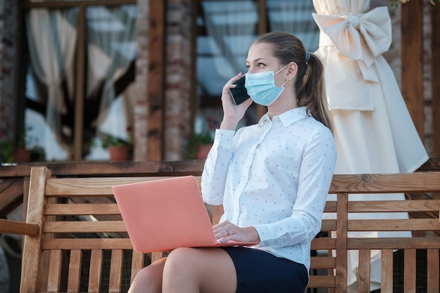 노트북 및 스마트 폰으로 벤치에 앉아 의료 마스크에 유럽 젊은 아가씨
