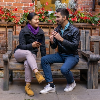 European young man talking to an asian girl holding a smartphone in her hands, sitting on a bench outdoors