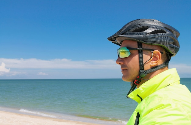European young sports man with grey bike helmet and colorful sunglasses is looking away on blue ocean or sea background. profile of cyclist with copy space