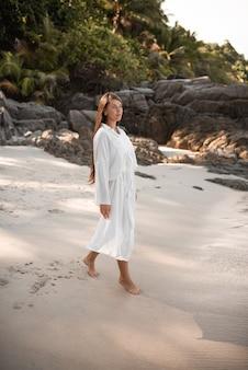 유럽의 젊은 황갈색 여성들은 휴식을 취하고 하얀 모래 해변에서 뛰었습니다. 긴 검은 밤나무 머리카락. 흰색면 옷. boho 스타일의 드레스. 태국. 아쿠아 마린 크리스탈 바다