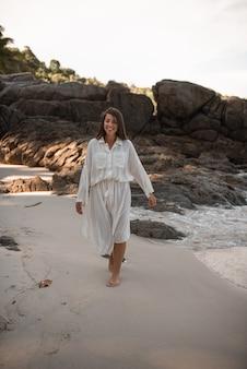 Европейские молодые загорелые женщины отдыхают и бегают по белому песчаному пляжу.