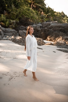 European young tan women have rest and run on white sand beach.