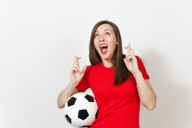 유럽의 젊은 여성 축구 팬이나 빨간 유니폼을 입은 선수는 흰색 배경에 격리된 축구공을 잡고 손가락을 꼬고 있습니다. 스포츠 플레이 축구 라이프 스타일 개념입니다. 특별한 순간을 기다리세요. 소원을 빌다