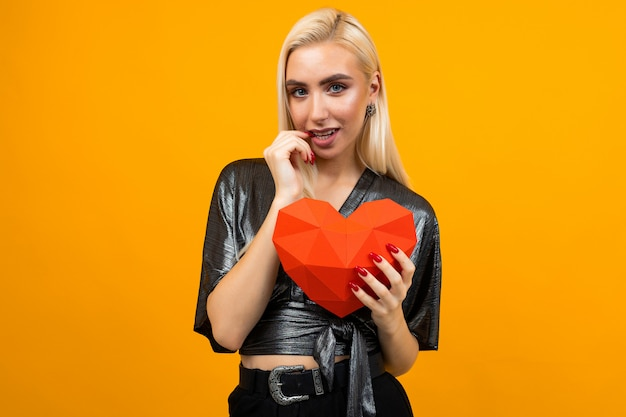 European young woman holding a 3d heart figure in her hands on an orange studio space. valentine's day