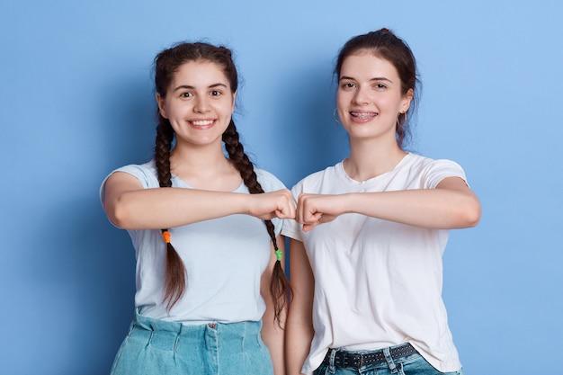 ヨーロッパの若い女性はお互いに拳バンプを与える