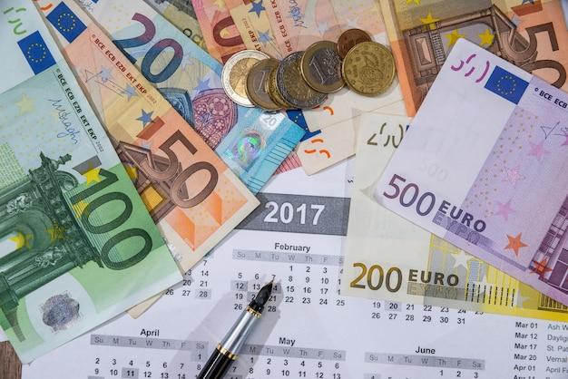 Euros bills on 2017 calendar with pen.