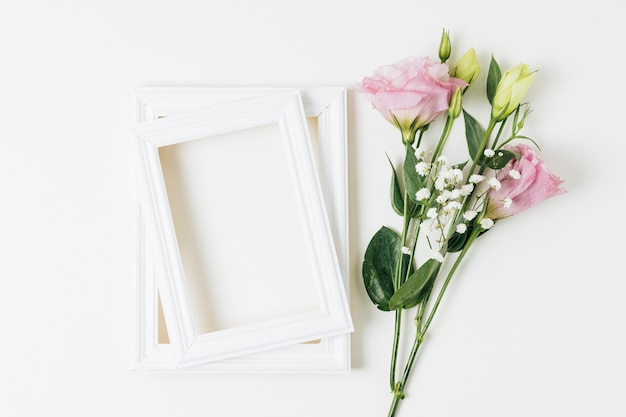 Eustoma and baby's-breath flowers near the wooden frame on white background