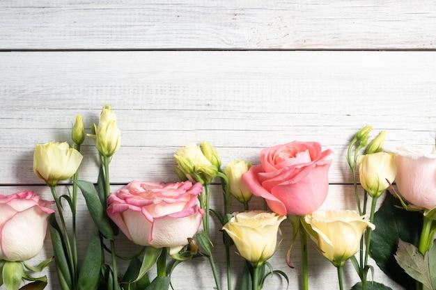 ユーストマの花とビンテージスタイルの木製の背景にピンクのバラ。ロマンチックな結婚式の背景。