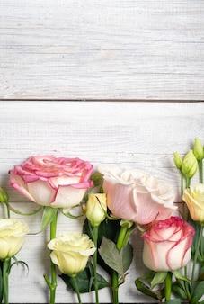 Цветы эустомы и розовые розы на деревянных фоне в винтажном стиле. романтический свадебный фон.