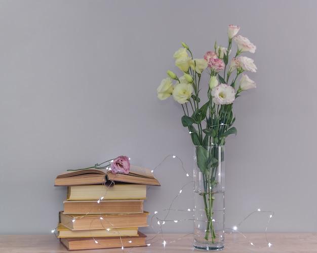Букет цветов эустомы в вазе, стопка старых старинных книг и гирлянды. чтение и расслабление концепции.