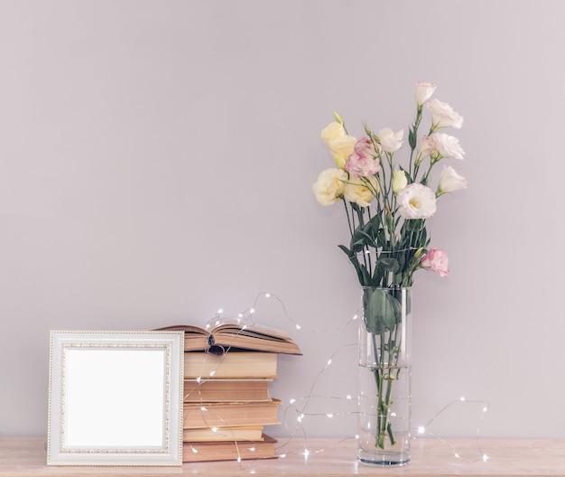 꽃병에 eustoma 꽃 꽃다발, 오래 된 빈티지 책의 스택, 회색 배경에 흰색 사진 프레임 및 갈 랜드 조명. 개념을 읽고 휴식을 취하십시오.