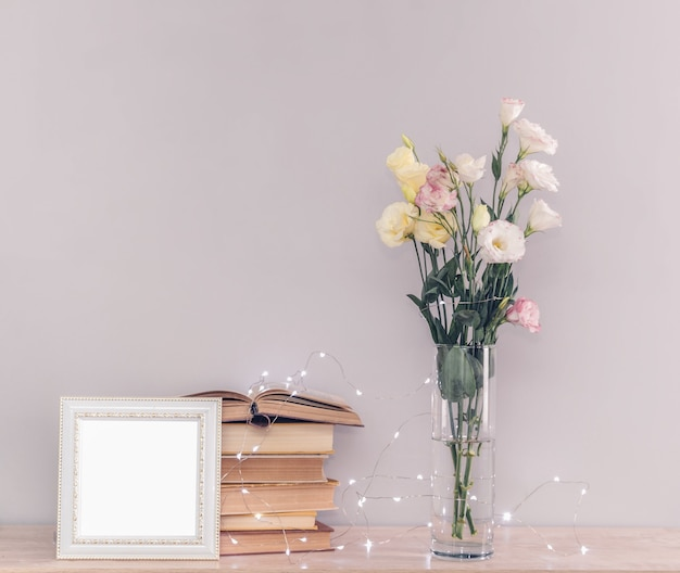 Eustoma flowers bouquet in a vase, stack of old vintage books, white photo frame and garland lights on a grey background. reading and relax concept.