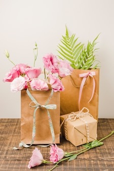 Eustoma flowers in brown paper bag with gift box on wooden surface against white wall