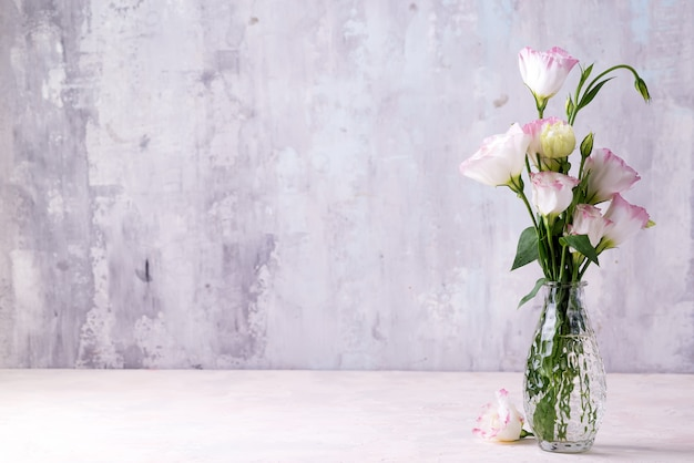 Eustoma flowers in vase on table near stone wall, space for text.