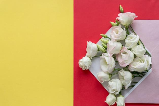 Эустома цветы с конвертом на красочный фон. открытый конверт с белыми цветочными композициями. праздничное приветствие концепции. яркая свежая композиция