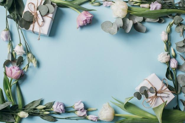 Eustoma, эвкалипт, тюльпаны и подарочные коробки на синем фоне