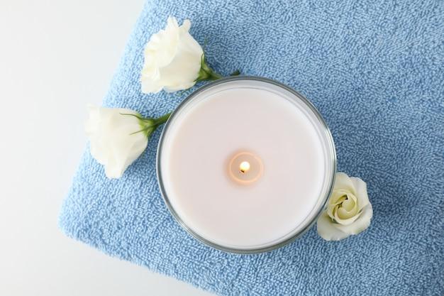 Полотенце, свеча и eustoma на белой предпосылке, взгляд сверху. концепция спа