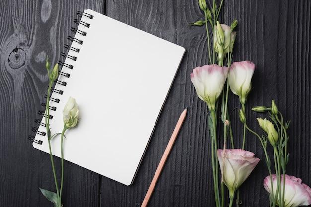木製の机の上に鉛筆と空の螺旋状のメモ帳と紫色のeustoma花の束