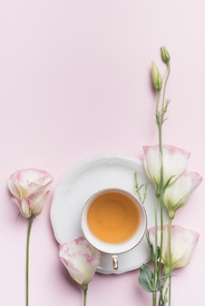 ピンクの背景に紅茶のカップと美しいeustoma花のクローズアップ